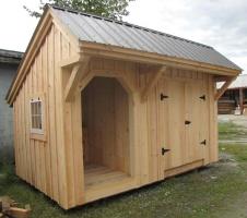 Двускатная крыша, отделка - доска. Двустворчатая дверь.